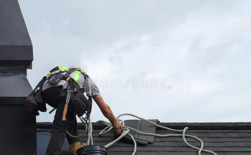 Roof repair construction worker roofer man roofing security rope royalty free stock image