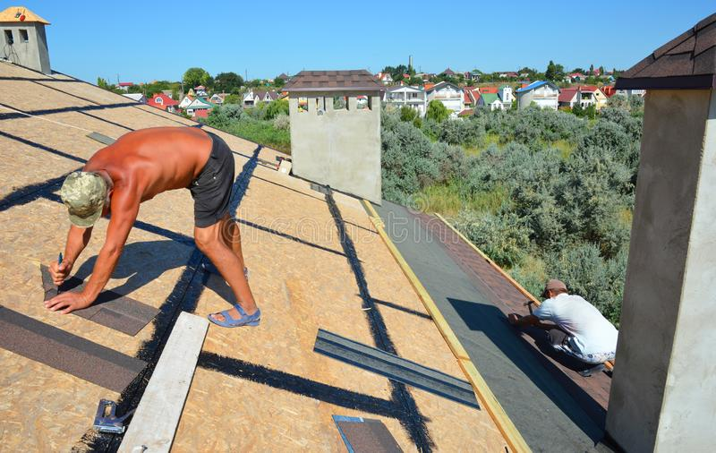 Roofer contractors laying and installing asphalt shingles. Roof asphalt shingles installation with two roofers. Roofing royalty free stock image