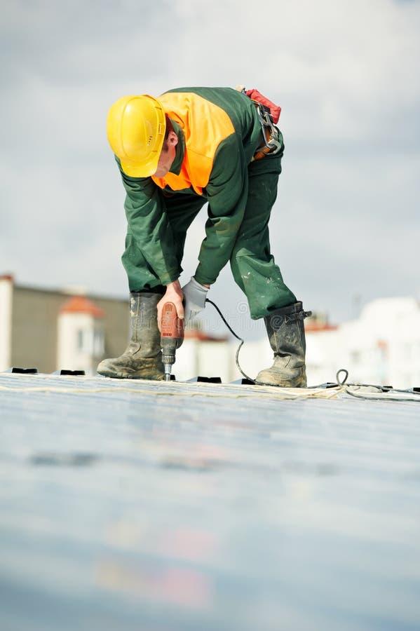 Roofer de constructeur de travailleur au travail de profil en métal images stock