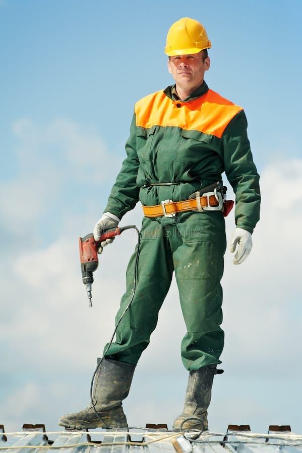 Roofer del constructor del trabajador en el trabajo del perfil del metal foto de archivo libre de regalías