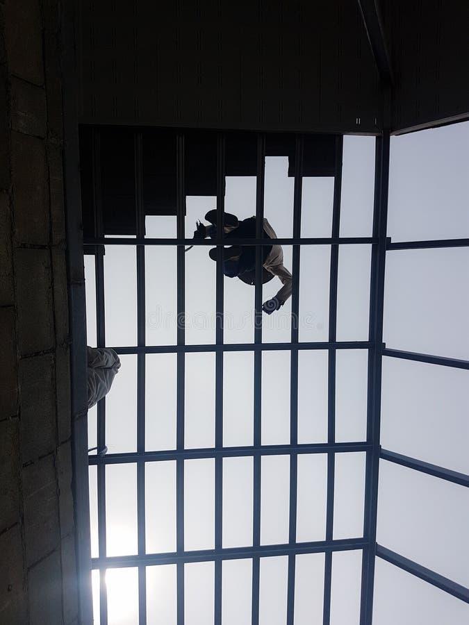 Roofer della siluetta che lavora al tetto fotografia stock libera da diritti