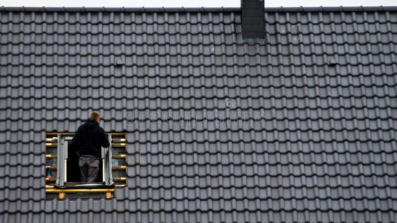 Roofer, der Dachbodenfenster installiert lizenzfreie stockfotografie