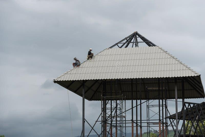 Roofer die aan de bovenkant van het onvolledige dak werken royalty-vrije stock foto's