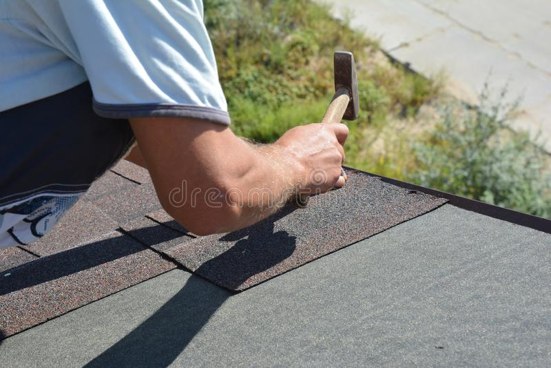 Roofer die Asphalt Shingles installeren op de hoek van het de Bouwdak van het huisdakwerk met hamer en spijkers Dakwerkbouw dakwe stock afbeelding