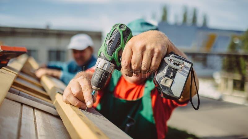 Roofer die een boor gebruiken maakt een GLB aan een huisdak vast stock foto's