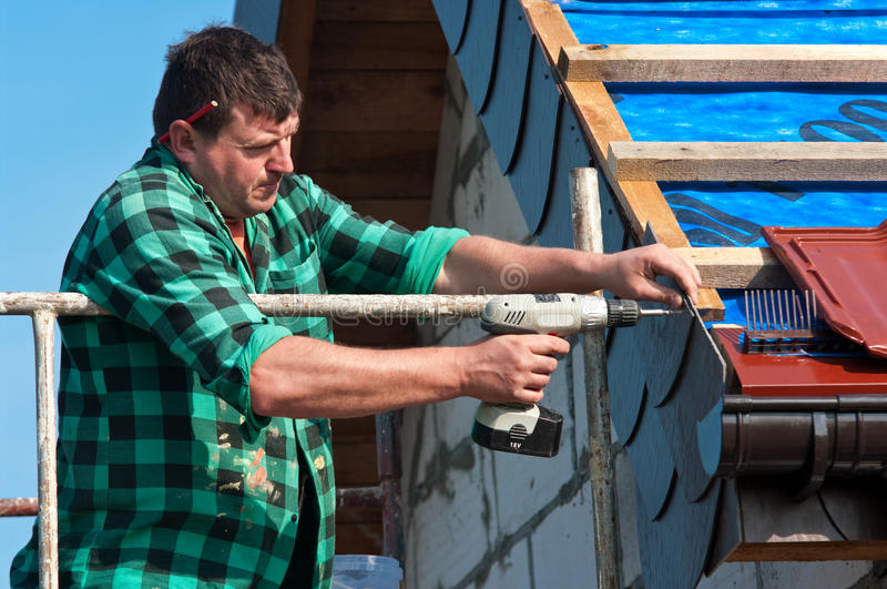 Roofer with drill. Roofer with a drill installing roof tiles stock image