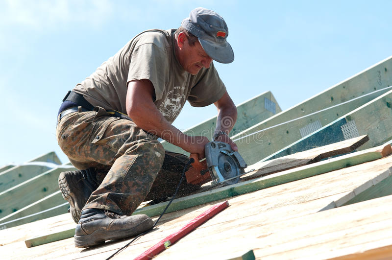 Roofer with Electric Saw. Roofer at work on top of a house using an electric saw royalty free stock images
