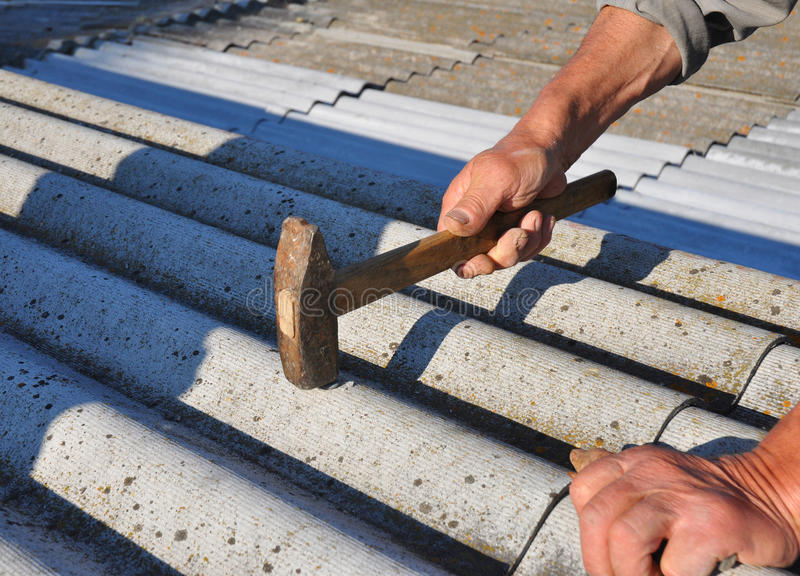 Roofer hammering nail in asbestos old roof tiles. Roofing construction royalty free stock photo