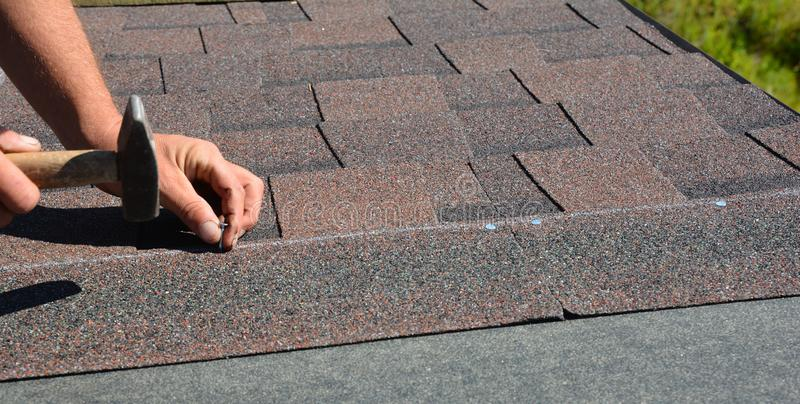 Roofer hands installing asphalt shingles on house construction roof corner with hammer and nails.  Roofing Construction Panorama. Photo photo royalty free stock photos
