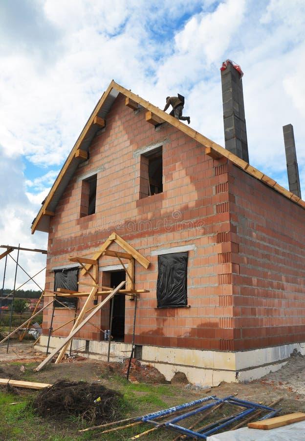 Roofer Install Bitumen Tiles auf der Dachspitze Deckung Constructio stockbild