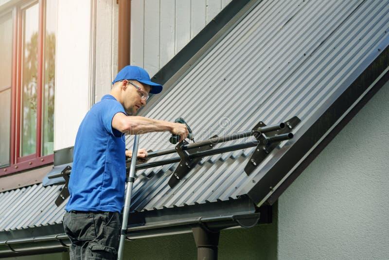 Roofer installant la garde de neige sur le toit en métal photos stock