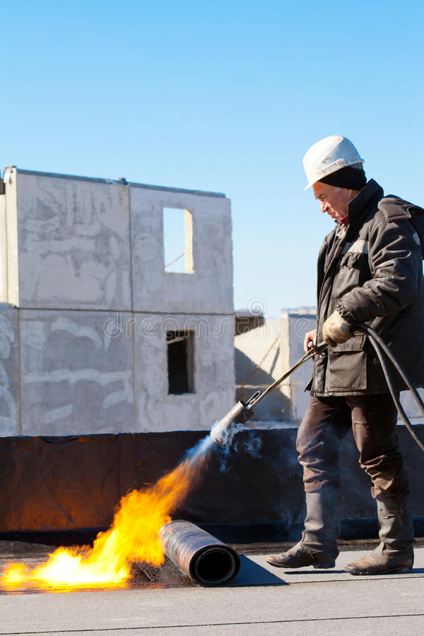 Roofer installing a roll of roofing felt. Roofer man worker in protective gear installing a roll of roofing felt by means of gas blowpipe torch stock photos
