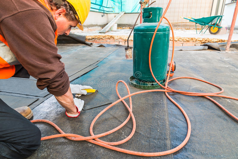 Roofer installing rolls of bituminous waterproofing membrane for the waterproofing of a terrace royalty free stock images
