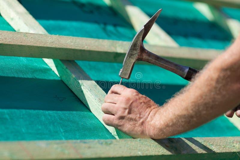 Roofer martelant un clou sur les faisceaux de toit photo libre de droits