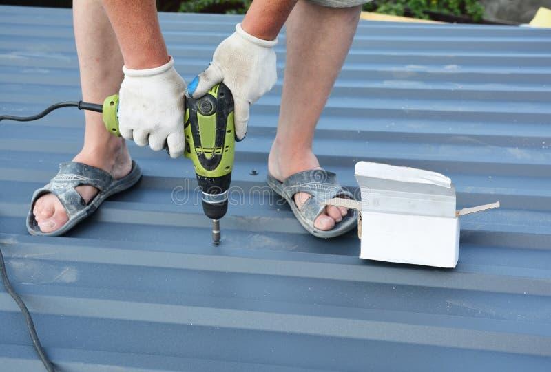 Roofer mit Schraubengewehr, die Leichtmetall-Dachziegel-Dachziegel einbauen stockbilder