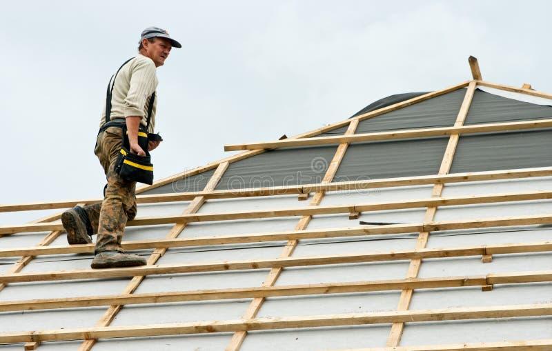 Roofer op het werk aangaande dak stock fotografie