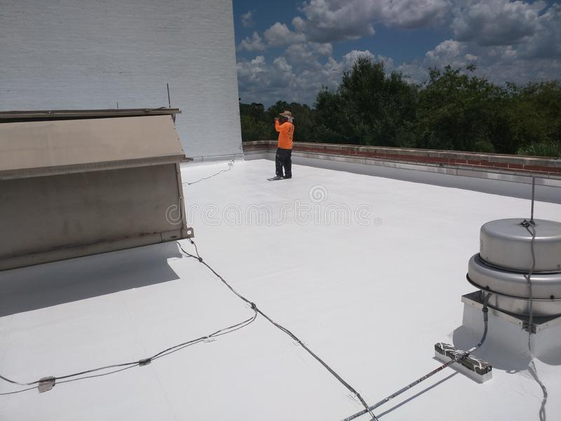 Roofer que inspeciona um telhado liso comercial, telhado de EPDM imagem de stock