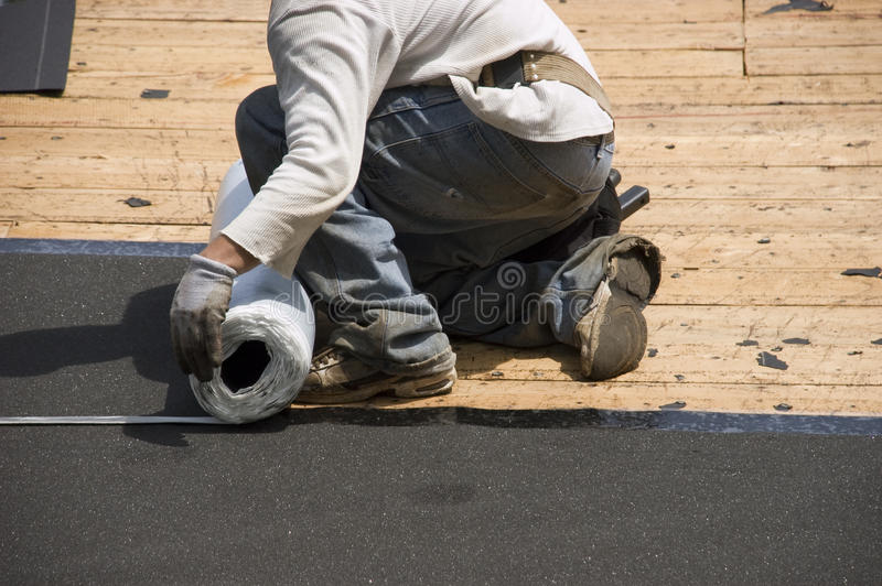 Roofer on Roof, Ice Shield Tar Paper Shingles stock photo
