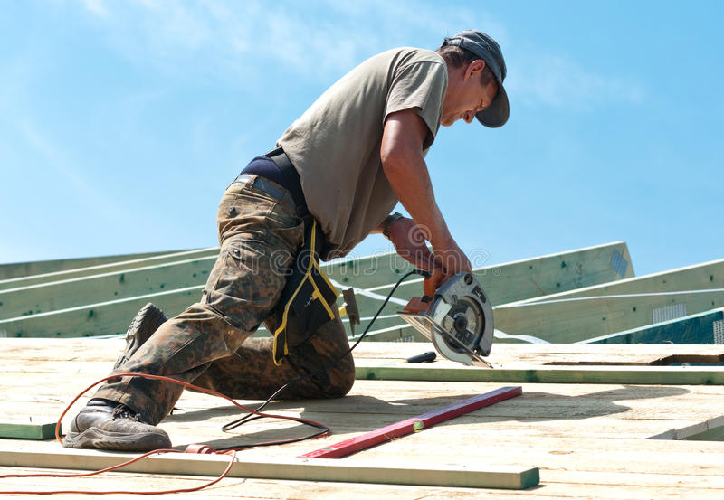 Roofer with rotary drill. Worker (roofer) on rooftop using rotary drill royalty free stock photography