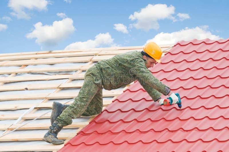 Roofer screwdriving metal tiling stock images