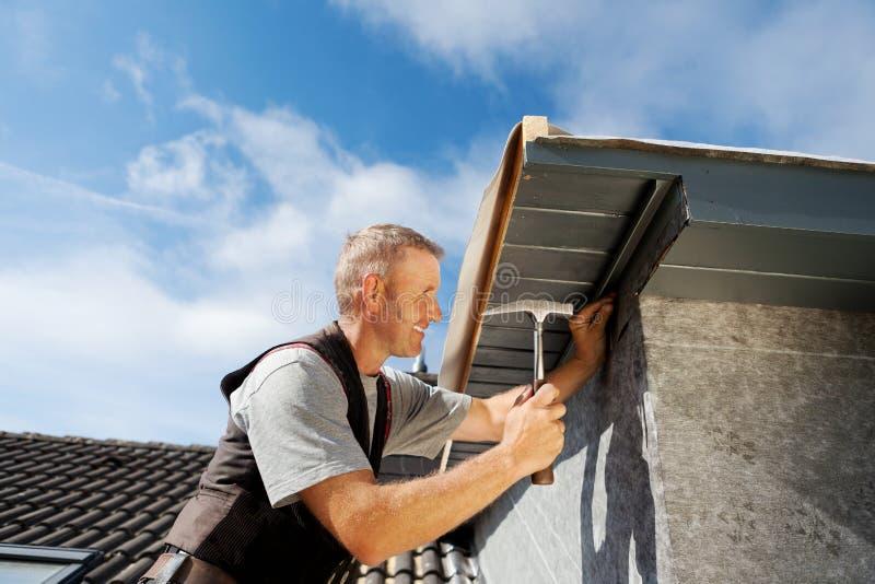 Roofer som arbetar på en ny vindskupefönster royaltyfri foto