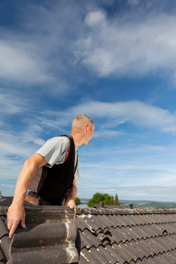 Roofer som arbetar på ett gammalt tak arkivbild