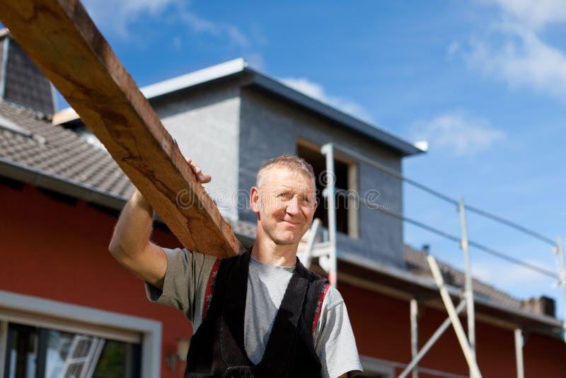Roofer som bär en wood planka över hans skuldra royaltyfri foto