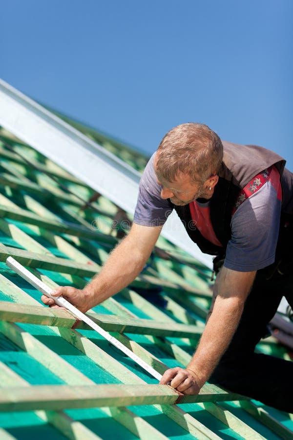 Roofer som mäter takstrålarna arkivbild