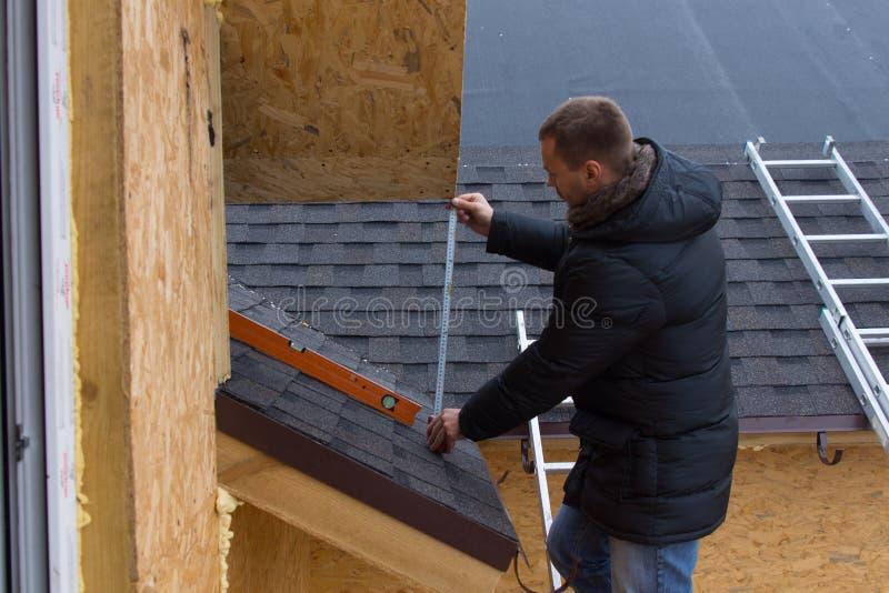 Roofer som mäter tegelplattor på ett nytt hus royaltyfri foto