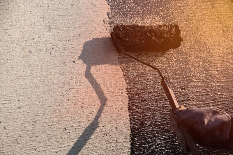 Roofer worker painting black coal tar or bitumen at concrete. Industrial worker on construction site laying sealant for waterproofing cement. Black roof coating stock photography