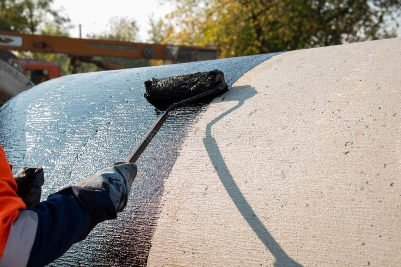 Roofer worker painting black coal tar or bitumen at concrete. Surface by the roller brush, A waterproofing. industrial worker on construction site laying royalty free stock image