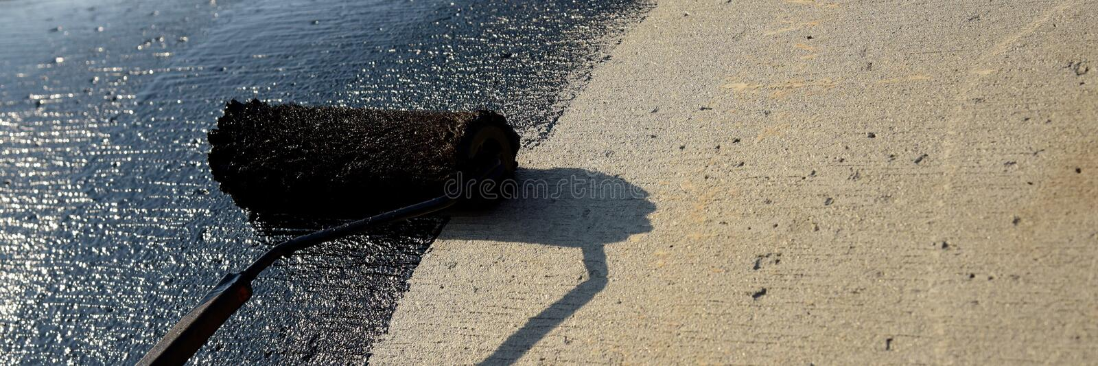 Roofer worker painting black coal tar or bitumen. At concrete surface by the roller brush, A waterproofing. industrial worker on construction site laying stock images