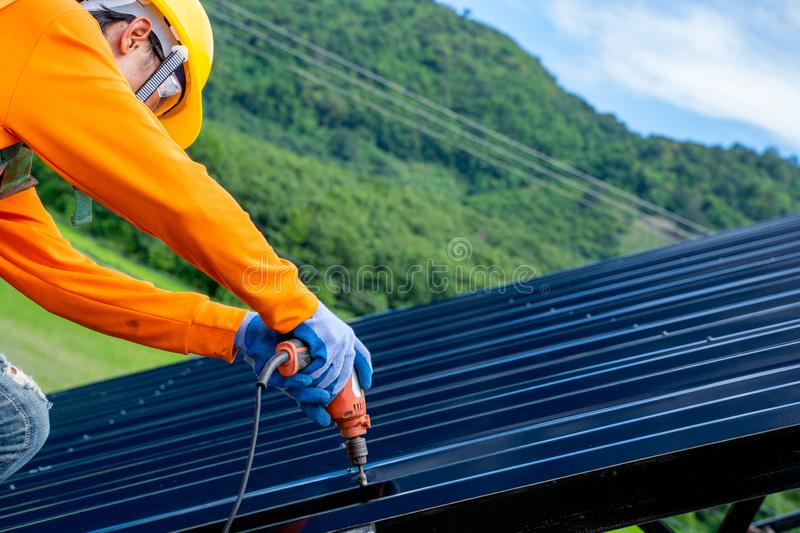 Roofer worker in protective uniform wear and gloves. Using air or pneumatic nail gun and installing asphalt shingle on top of the new roof,Concept of royalty free stock photos