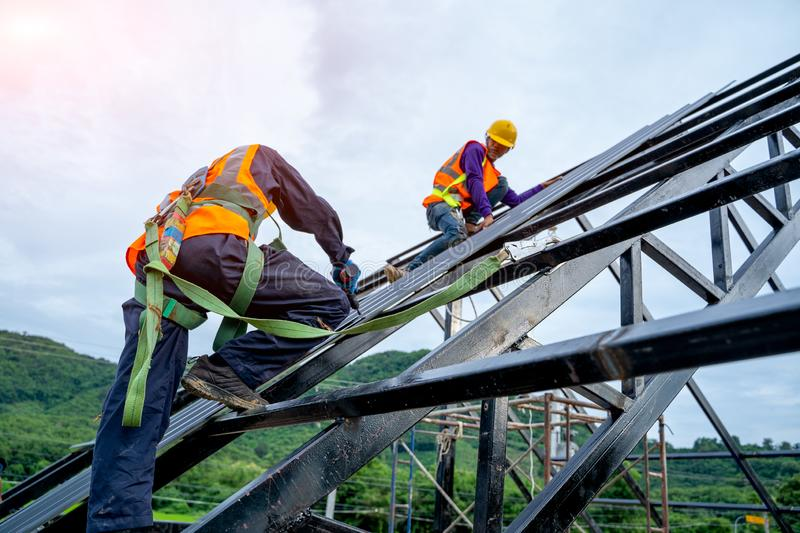 Roofer worker in protective uniform wear and gloves, using air or pneumatic nail gun and installing asphalt shingle on top roof stock image