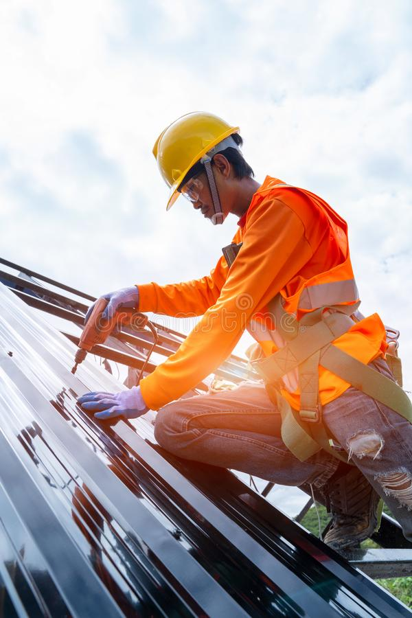 Roofer worker in protective uniform wear and gloves royalty free stock photography