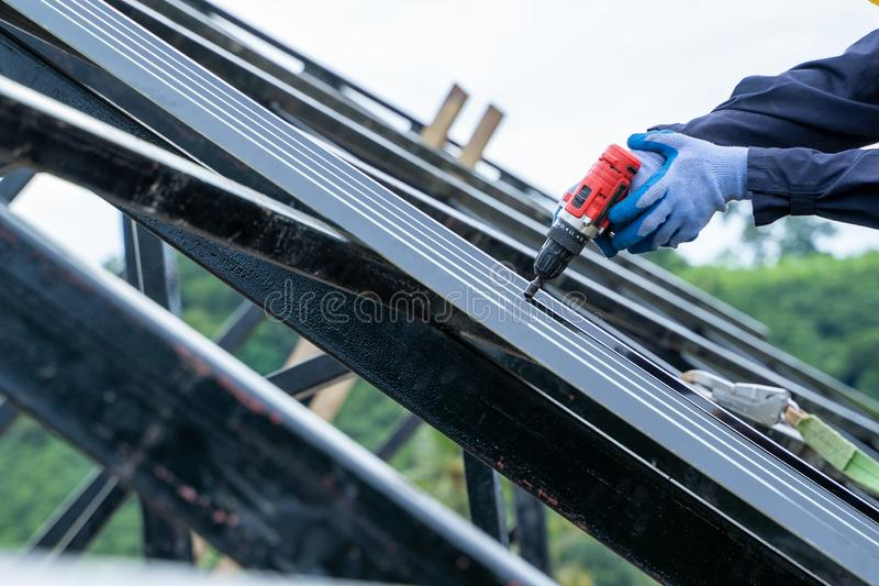 Roofer worker in special protective work wear and gloves,Using pneumatic gun and installing Metal Sheet on top. royalty free stock photography