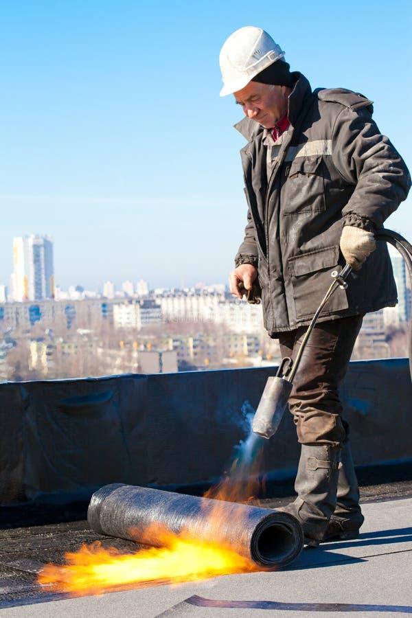 Rooferarbeitskraft, die eine Rolle des Dachfilzes installiert lizenzfreie stockfotografie