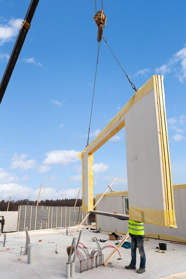Rooferbyggmästarearbetare med kranen som installerar den strukturella isolerade panelSMUTTEN Byggande energi-effektivt hus för ny fotografering för bildbyråer