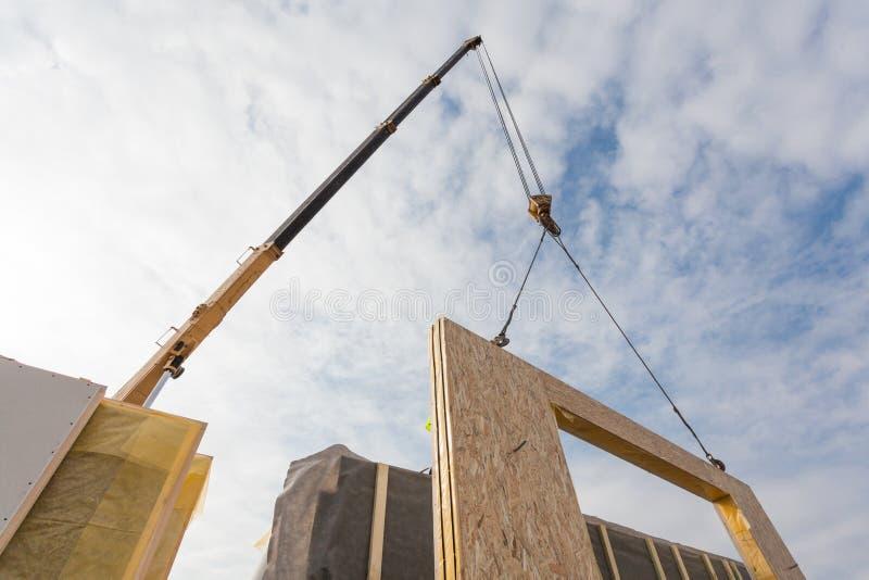 Rooferbyggmästarearbetare med kranen som installerar den strukturella isolerade panelSMUTTEN Byggande energi-effektivt hus för ny royaltyfria foton