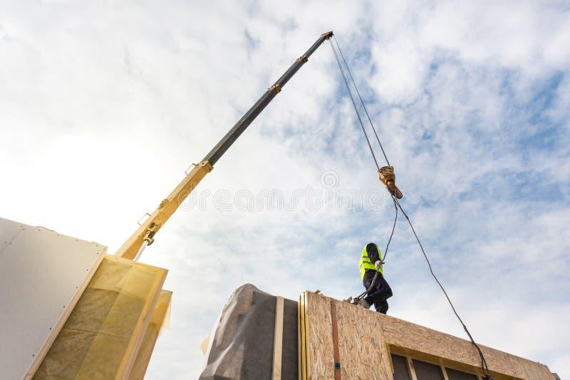 Rooferbyggmästarearbetare med kranen som installerar den strukturella isolerade panelSMUTTEN Byggande energi-effektivt hus för ny royaltyfria bilder