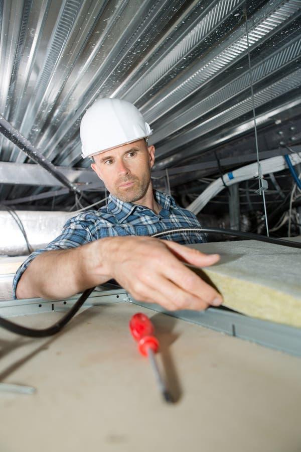 Roofererbauerarbeitskraft, die Dachisoliermaterial installiert lizenzfreie stockfotos