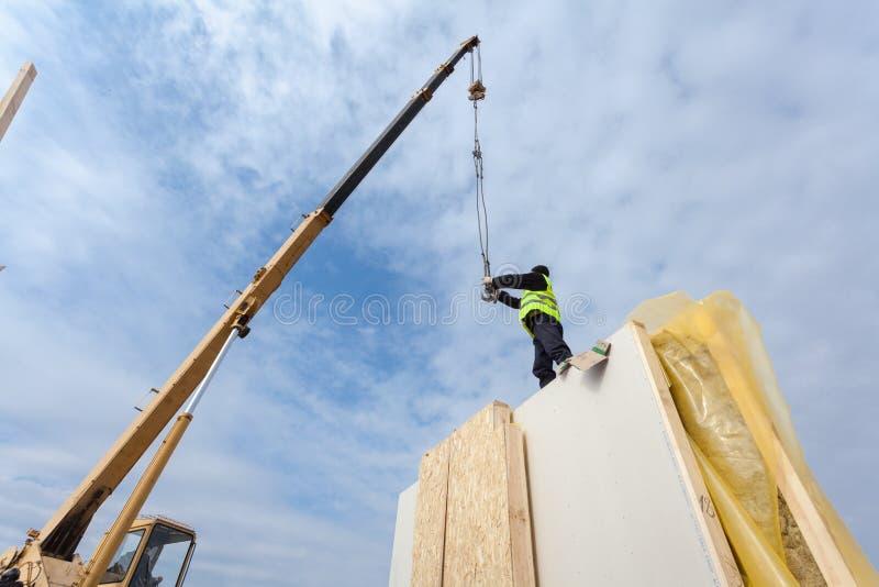 Roofererbauerarbeitskraft mit dem Kran, der strukturelle Isolierplatten installiert, NIPPEN Errichtendes Energiesparendes Haus de lizenzfreie stockfotografie