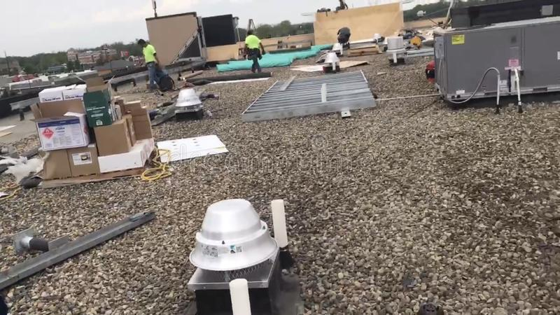 Roofers που επισκευάζει τους τομείς μιας εμπορικής επίπεδης στέγης και των υλικών, των εργαλείων και των προμηθειών στοκ φωτογραφία με δικαίωμα ελεύθερης χρήσης