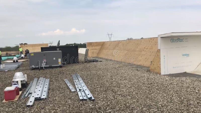 Roofers и экипаж ремонтируя коммерчески плоскую крышу и материалы, инструменты и поставки стоковое фото