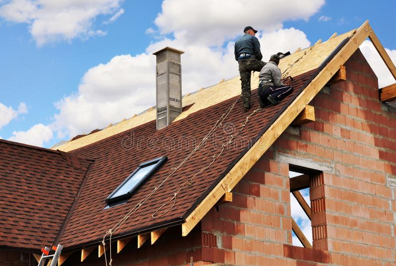 Roofers lay and install asphalt shingles. Roof repair with two roofers. Roofing construction with roof tiles, asphalt shingles. royalty free stock photos