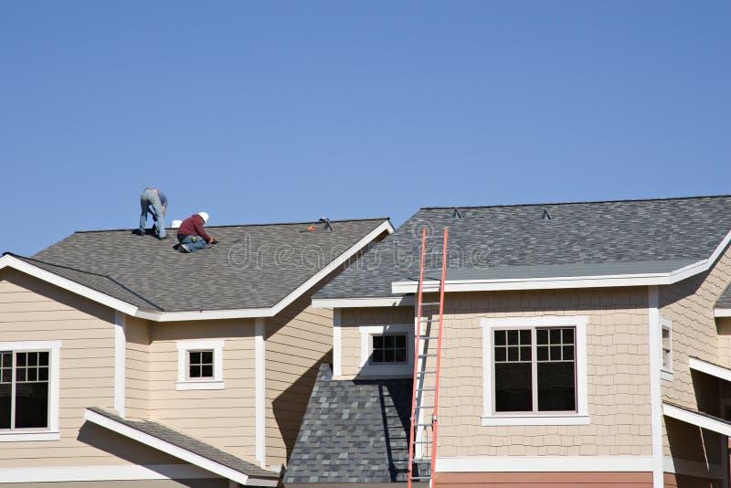 Roofers travaillant au toit neuf image stock