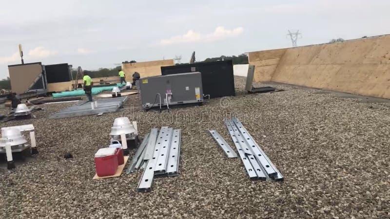 Roofers und eine Mannschaft, die ein Handelsflachdach und Materialien, Werkzeuge und Versorgungen repariert lizenzfreie stockfotos