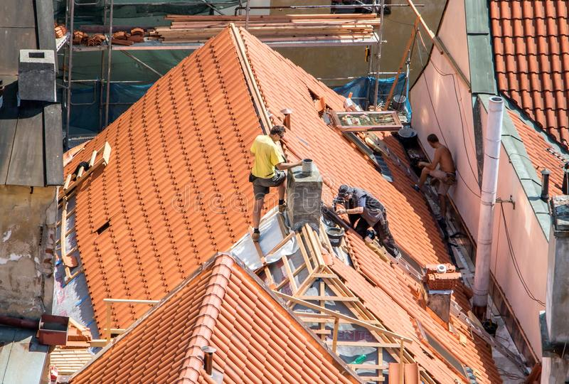 Roofers working on the repair of historic roofs. Replacement of roof tiles. Prague, Czech republic royalty free stock photos