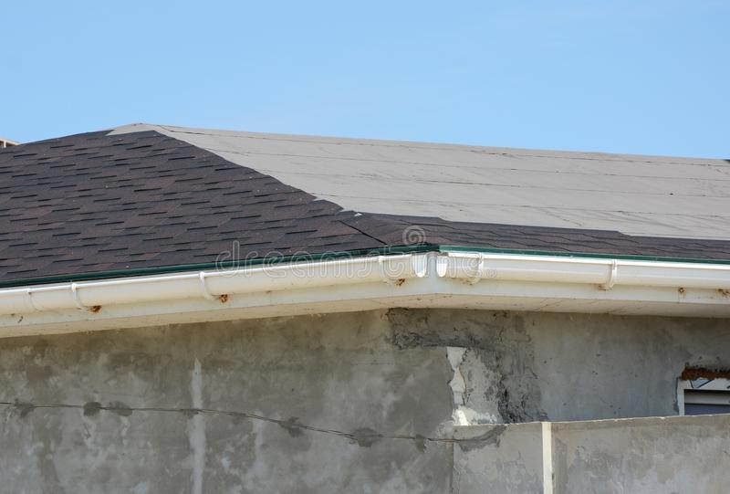 Roofing constraction. Install house roof gutter and laying asphalt shingles. Roof repair royalty free stock photos