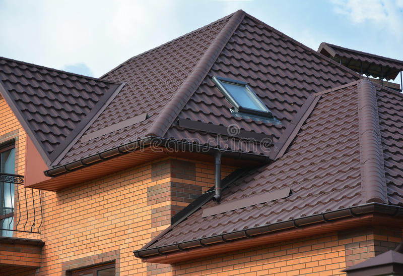Roofing construction with attic skylights, rain gutter system and roof protection from snow. Hip and Valley roofing types. stock photo